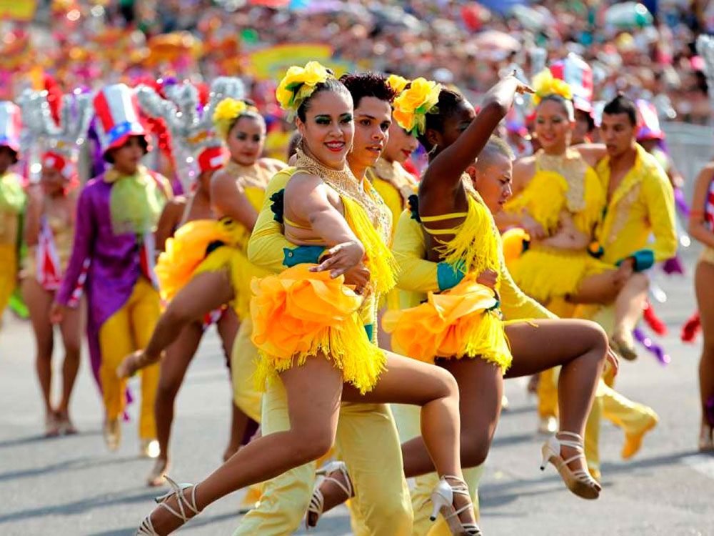 Image of a couple dancing salsa on the streets during feria de Cali wearing extravagant yellow costumes with feathers.