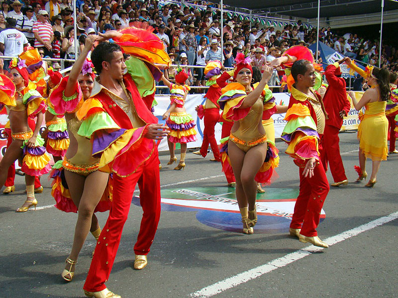 Image of couple dancing on the street during feria de cali wearing colourful costumes and doing interesting turns