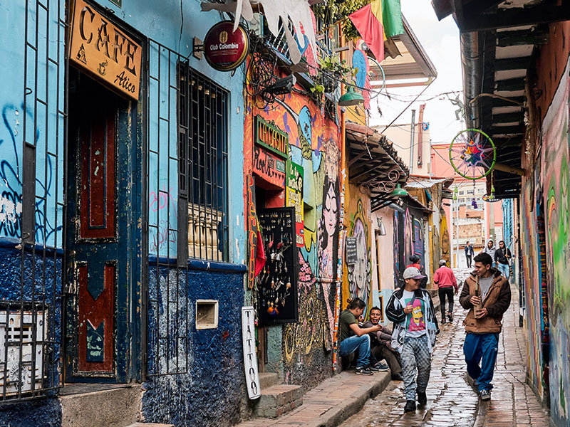 a picture of Bogota's colourful streets, houses painted in bright colours, people walking and smiling multiple plants and decorations on the facades