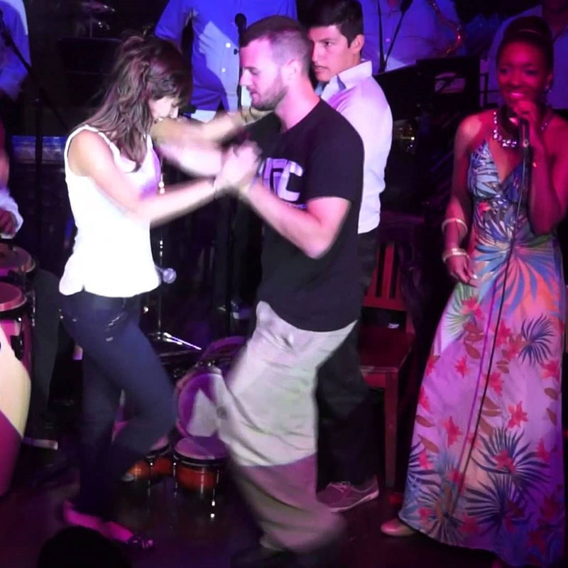 Couple dancing on stage at one the best salsa clubs in Bogota with a live orchestra in the background.